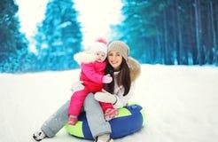 Glückliche Mutter und Kind, die auf Schlitten im Winter sitzt Stockfotografie