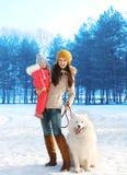 Glückliche Mutter und Kind, die mit weißem Samoyedhund im Winter geht Stockfotografie