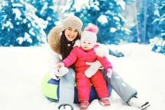Glückliche Mutter und Kind, die zusammen auf Schlitten am Wintertag sitzt Stockfoto