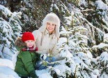 Glückliche Mutter und Kind draußen unter schneebedeckten Fichten stockbild