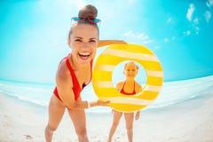 Glückliche Mutter und Kind mit gelbem aufblasbarem Rettungsring auf Strand lizenzfreies stockbild