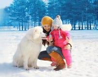 Glückliche Mutter und Kind mit weißem Samoyedhund im Winter Stockfotografie