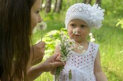 Glückliche Mutter und kleine Tochter im Park Lizenzfreie Stockfotos