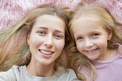 Glückliche Mutter und kleine Tochter mit dem blonden Haar, das auf rosa Pelz liegt und selfie macht Zwei schöne Leute, Familienko lizenzfreie stockfotografie