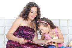 Glückliche Mutter und kleines Mädchen, die ein Buch liest Stockfotografie