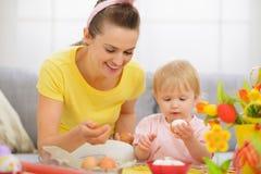 Glückliche Mutter und Schätzchen, die Ostereier isst Stockbild