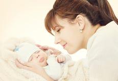 Glückliche Mutter und schlafendes neugeborenes Baby, Mutter, die zu neugeborenem schaut stockfoto