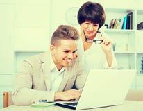 Glückliche Mutter und Sohn betrachten Software auf Laptop Stockfotos