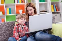Glückliche Mutter und Sohn, der Computer verwendet Stockbilder