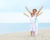Glückliche Mutter und Sohn, die auf dem Strand steht Stockbild