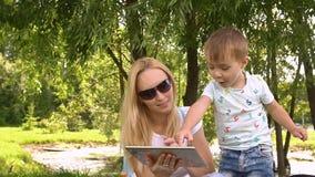 Glückliche Mutter und Sohn, die auf Tablet-Computer spielt Langsame Bewegung stock video footage