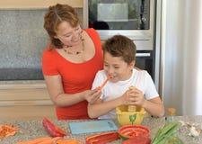 Glückliche Mutter und Sohn, die das Mittagessen mit einem Mörser vorbereitet stockfotos