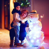 Glückliche Mutter und Sohn, die draußen Winterurlaube mit Schneemann feiert Stockbild