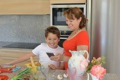 Glückliche Mutter und Sohn, die ein Rezept im Handy wiederholt stockbild