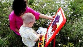 Glückliche Mutter und Sohn malen Farben in der Natur stock video