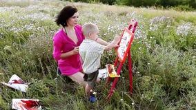 Glückliche Mutter und Sohn malen Farben in der Natur stock footage