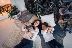 Glückliche Mutter und Tochter öffnende Weihnachtsgeschenke Familie trat um einen Baum zu Hause zusammen Weihnachtsbaum mit Gesche stockfotos
