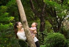 Glückliche Mutter und Tochter/Baby, das froh um einen Baum im Wald spielt Stockfotografie