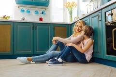 Glückliche Mutter und Tochter, die auf dem Boden sitzt Stockfotografie