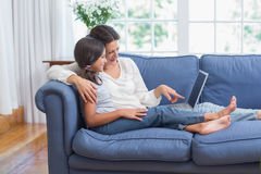 Glückliche Mutter und Tochter, die auf der Couch sitzt und Laptop verwendet Lizenzfreie Stockfotografie