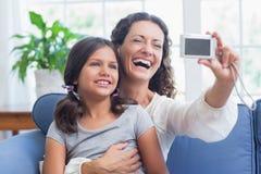 Glückliche Mutter und Tochter, die auf der Couch sitzt und selfie nimmt Lizenzfreie Stockfotos