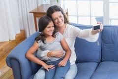 Glückliche Mutter und Tochter, die auf der Couch sitzt und selfie nimmt Lizenzfreie Stockfotografie