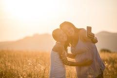 Glückliche Mutter und Tochter, die draußen selfie durch Smartphone nimmt Stockfotografie