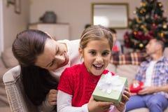 Glückliche Mutter und Tochter, die ein Geschenk hält Stockfotos