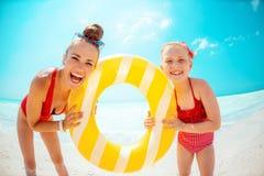 Glückliche Mutter und Tochter, die gelben aufblasbaren Rettungsring hält lizenzfreie stockbilder