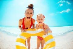 Glückliche Mutter und Tochter, die gelben aufblasbaren Rettungsring hält stockfotografie