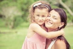 Glückliche Mutter und Tochter, die im Park zur Tageszeit spielt Stockfotografie