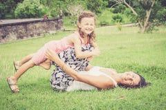 Glückliche Mutter und Tochter, die im Park zur Tageszeit spielt Stockfotos