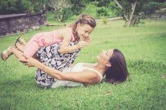 Glückliche Mutter und Tochter, die im Park zur Tageszeit spielt Stockfoto
