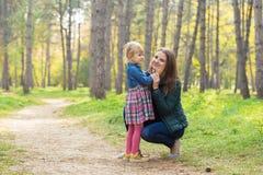Glückliche Mutter und Tochter, die mit ihrer Tochter im Park spricht stockbild