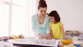 Glückliche Mutter und Tochter, die zu Hause Plätzchen macht stock footage