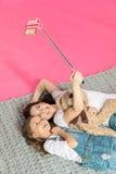 Glückliche Mutter und Tochter, die zusammen liegt und selfie nimmt Stockbilder