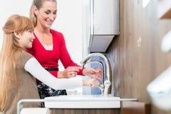 Glückliche Mutter und Tochter, die zwei Badezimmerwannen vergleicht Lizenzfreie Stockfotografie