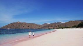 Glückliche Mutter und Tochter gehen auf rosa Strand stock video