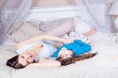 Glückliche Mutter und Tochter legen in Bett und in Habenspaß lizenzfreie stockfotos