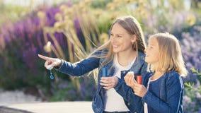 Glückliche Mutter und Tochter mit Seifenblasen Stockbild