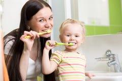 Glückliche Mutter und Tochter scherzen bürstende Zähne des Mädchens lizenzfreie stockfotos