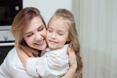 Glückliche Mutter und Tochter umarmen zu Hause lizenzfreie stockfotos