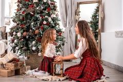 Glückliche Mutter- und Tochtersitzplätze nahe Tannenbaum stockbild