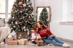 Glückliche Mutter- und Tochtersitzplätze nahe Tannenbaum lizenzfreie stockfotos
