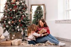 Glückliche Mutter- und Tochtersitzplätze nahe Tannenbaum stockfotos