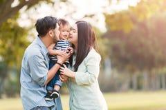Glückliche Mutter und Vater, die seinen kleinen Sohn im Park küsst lizenzfreie stockfotografie