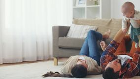 Glückliche Mutter und Vater, die zu Hause mit Baby spielt stock video