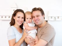 Glückliche Mutter und Vater, die zu Hause nettes Baby hält Stockbild