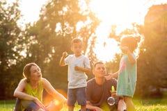 Glückliche Mutter und Vati, die mit Kindern draußen spielt stockfotografie