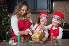 Glückliche Mutter und Zwillingsmädchen im roten Herstellungsweihnachtslebkuchenhaus lizenzfreie stockfotos